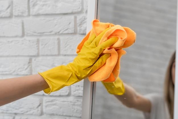 Espelho de limpeza de mulher com pano