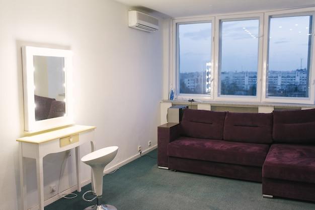 Espelho de maquiagem e sofá roxo no estúdio fotográfico