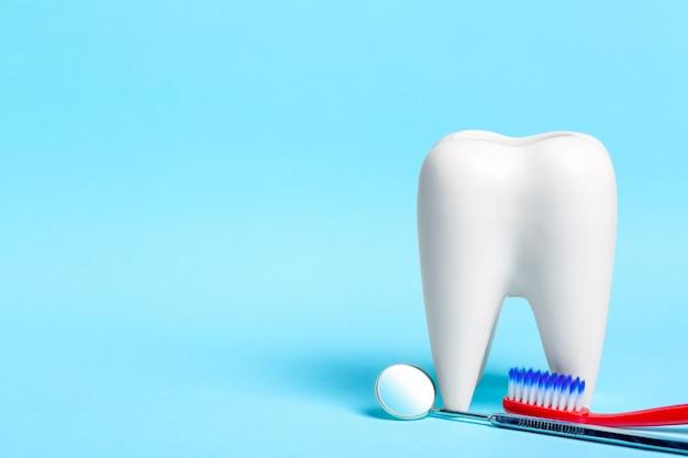 Espelho dental com escova de dentes perto de modelo de dente branco saudável sobre fundo azul claro.