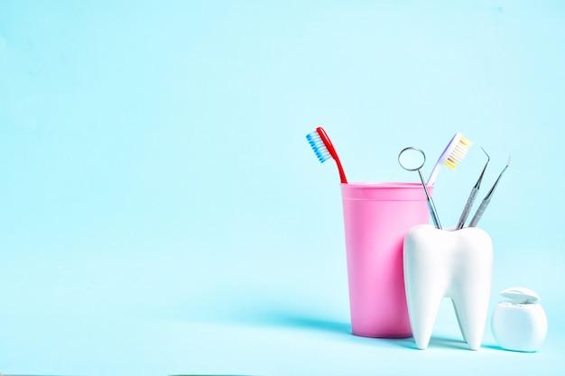 Espelho dental com sondas explorer no modelo saudável dente branco perto de fio dental e escovas de dentes em vidro rosa sobre fundo azul claro