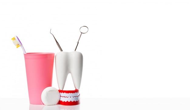 Espelho dental e instrumento dental do explorador no modelo branco do dente, na maxila humana e no fio dental perto da escova de dentes no vidro cor-de-rosa contra o fundo isolado branco.