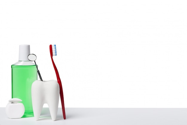 Espelho dental no modelo de dente branco perto de colutório, escova de dentes e fio dental contra fundo branco isolado.
