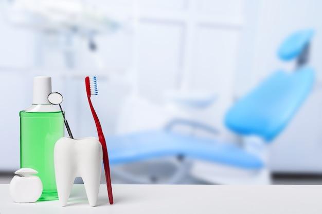 Espelho dentário em modelo de dente branco no consultório odontológico.