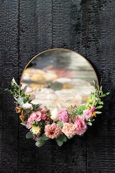 Espelho dourado com moldura floral em uma parede preta