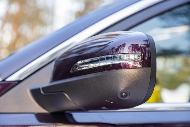 Espelho lateral da visão traseira de um carro moderno com uma câmera de visão do terreno, assistente de estacionamento e carro