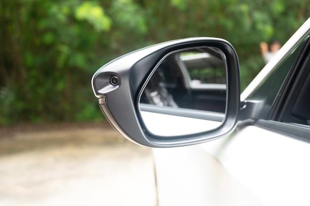Espelho lateral da visão traseira de um carro moderno com uma câmera de visão do terreno /