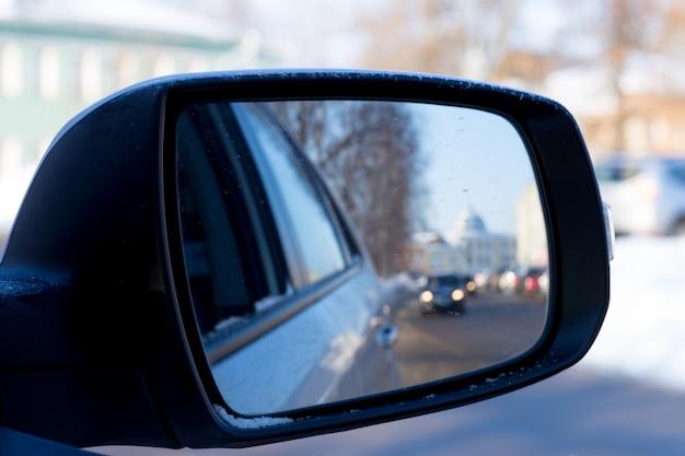 Espelho lateral preto do reflexo de um carro