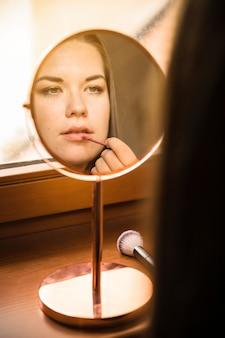 Espelho mão, com, reflexão, de, mulher, aplicando batom, ligado, dela, lábios