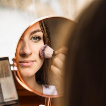 Espelho mão, com, reflexão, de, mulher, aplicando, blusher, ligado, dela, rosto
