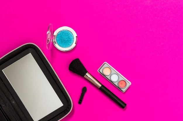 Espelho; pincel de maquiagem e sombra no fundo rosa