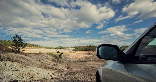 Espelho retrovisor do carro na planície com a floresta de pinheiros
