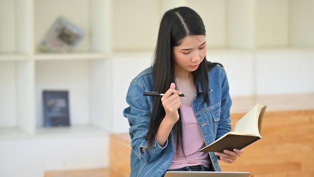 Espera de pensamento da jovem mulher que escreve no papel do caderno.