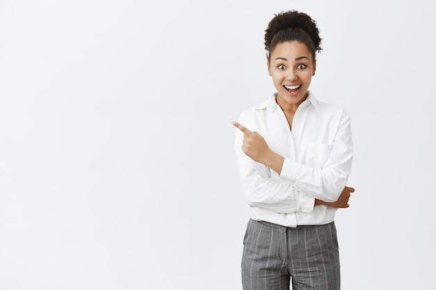 Esperançosa e feliz jovem afro-americana sorrindo alegre e apontando para o canto superior esquerdo