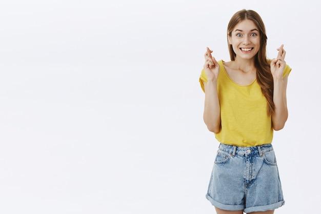 Esperançosa garota bonita sorrindo animada e cruzando os dedos boa sorte
