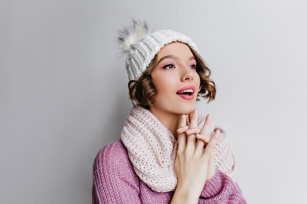 Esperançosa garota encaracolada de cabelos curtos com chapéu, olhando para longe. retrato de close-up interior de mulher muito morena, posando com lenço branco de malha.