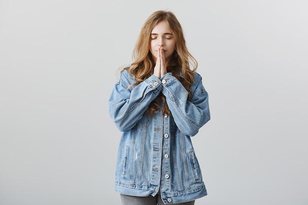 Esperançosa garota loira em jaqueta jeans fazendo um pedido, segurando as mãos em súplica, orando