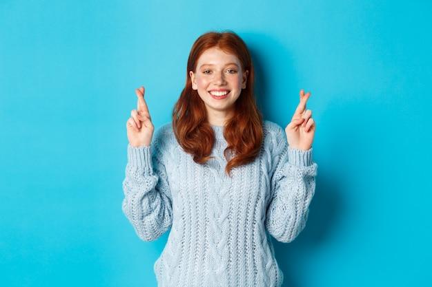 Esperançosa ruiva fazendo um desejo, cruze os dedos para dar boa sorte, sorrindo e antecipando boas notícias ou resultados positivos, em pé contra um fundo azul.