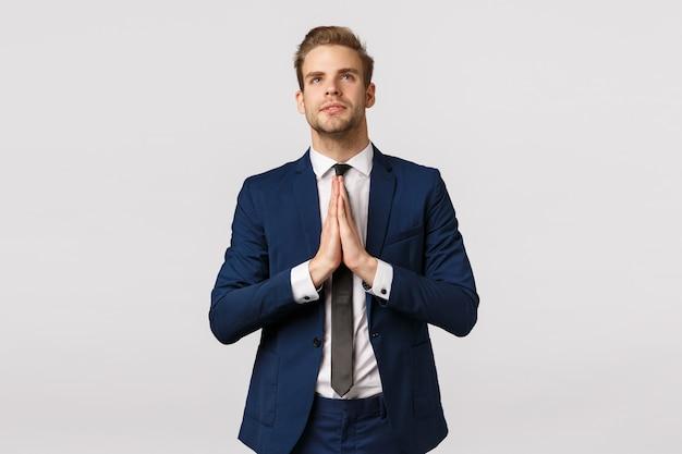 Esperançoso atraente loiro caucasiano, empresário masculino em terno clássico, roupa formal de negócios, de mãos dadas juntos em rezar, olhar o céu como crente, rezando, fazendo desejo