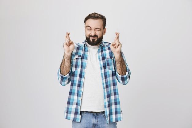 Esperançoso homem barbudo implorando, cruze os dedos boa sorte