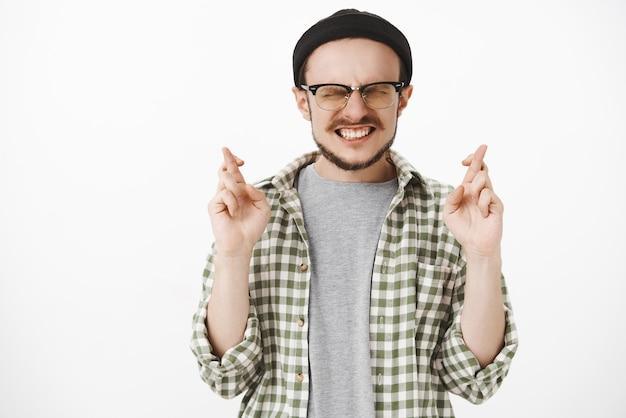Esperançoso intenso e fiel rapaz jovem bonito com barba de óculos e gorro hipster cerrando os dentes fechando os olhos cruzando os dedos para dar boa sorte