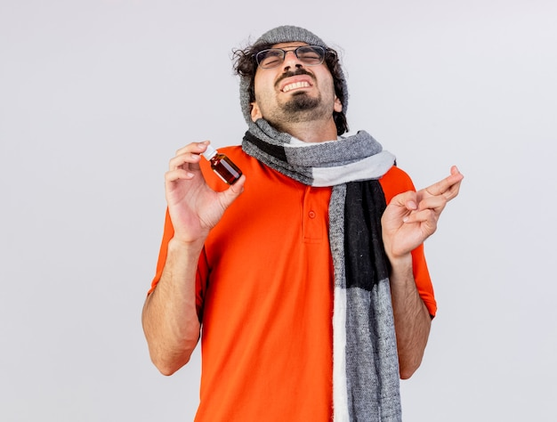 Esperançoso jovem doente usando óculos, chapéu de inverno e lenço segurando medicamento em um vidro cruzando os dedos desejando boa sorte com os olhos fechados, isolado na parede branca