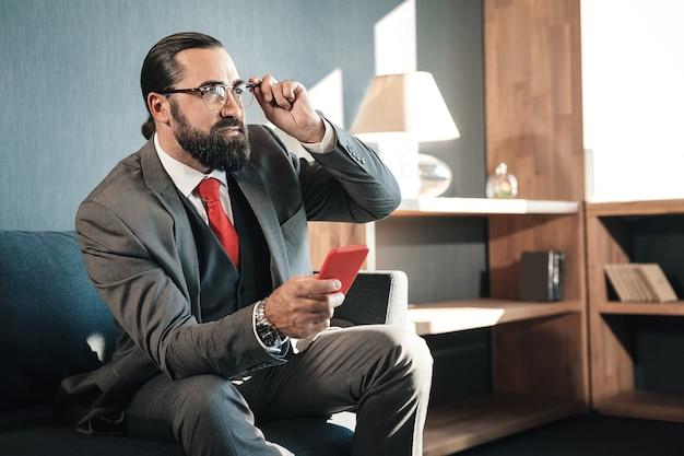 Esperando investidor. homem de negócios sério barbudo sentado no sofá enquanto espera pelo investidor