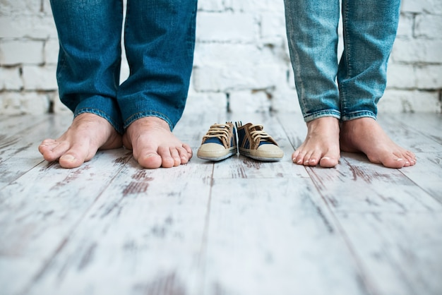 Esperando o bebê calçados infantis com os pés dos pais