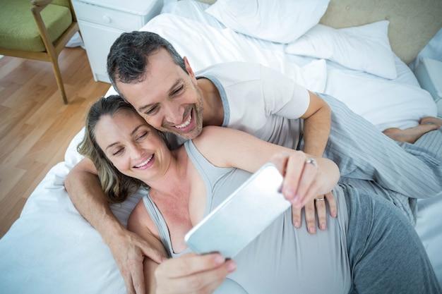 Esperando o casal deitado na cama e usando tablet digital