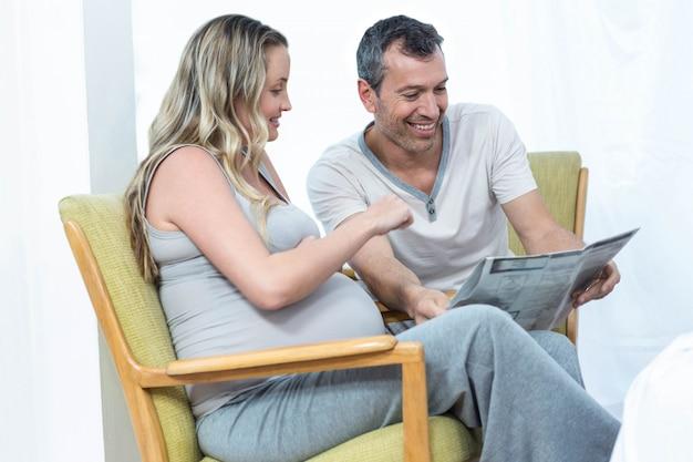 Esperando o casal sentado na cadeira e lendo jornal de notícias