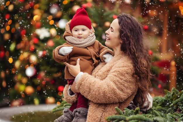 Esperando o feriado de ano novo. feliz alegre mãe com filhos em uma caminhada no inverno em uma rua decorada de natal.