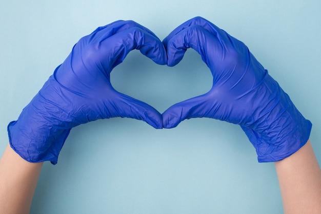 Esperando pelo melhor conceito. acima em cima, feche a foto das mãos gesticulando com um coração isolado sobre o fundo azul