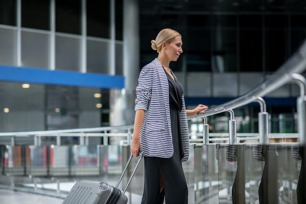 Esperando pelo vôo. perfil de mulher loira de negócios de meia idade com uma jaqueta listrada e uma mala esperando no terminal do aeroporto