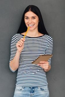 Esperando por inspiração. mulher jovem e atraente segurando um bloco de notas e carregando um lápis na boca em pé