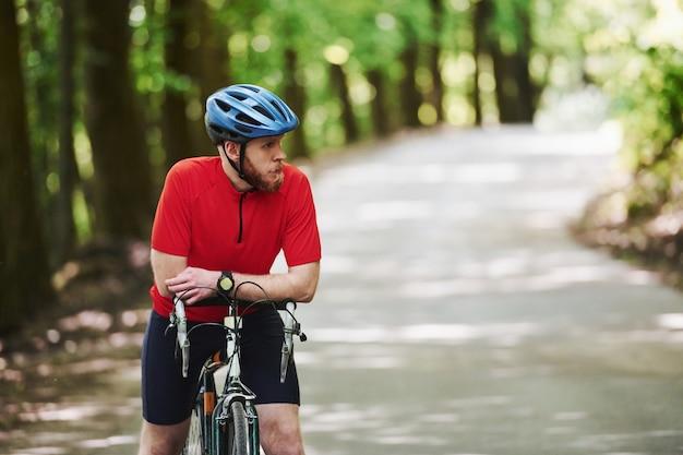Esperando por um amigo. ciclista de bicicleta está na estrada de asfalto na floresta em um dia ensolarado