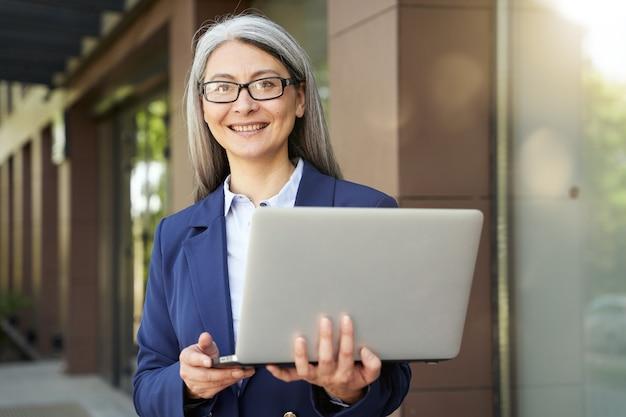 Esperando por um parceiro. retrato de mulher de negócios maduro lindo vestindo terno clássico e óculos, olhando para a tela do laptop em pé contra o prédio de escritórios ao ar livre. empresários no trabalho