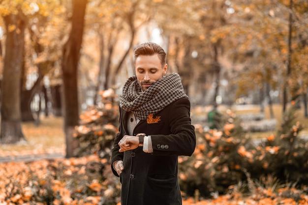 Esperando seu encontro, homem bonito olhando para o braço relógios vestindo casaco azul escuro e lenço. jovem