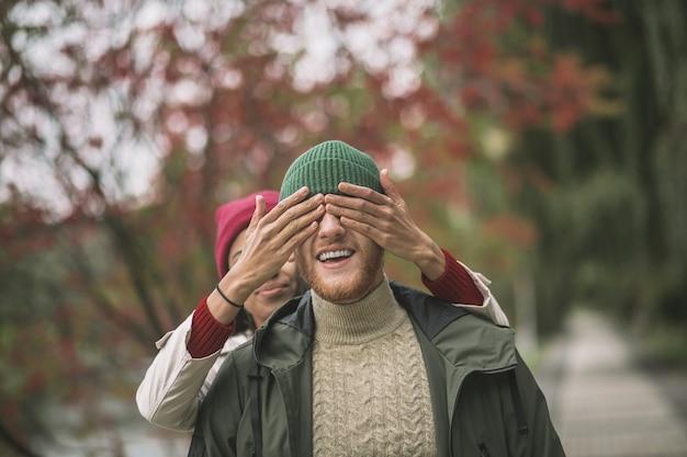 Esperando surpresa. uma mulher fechando os olhos do namorado enquanto caminhava