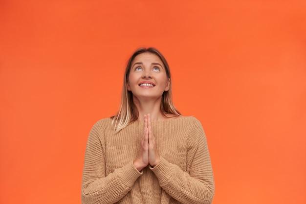 Esperando uma adorável jovem loira de cabelos curtos, mantendo as palmas das mãos levantadas juntas enquanto olha para cima sonhadoramente, isolada sobre uma parede laranja em um suéter de malha
