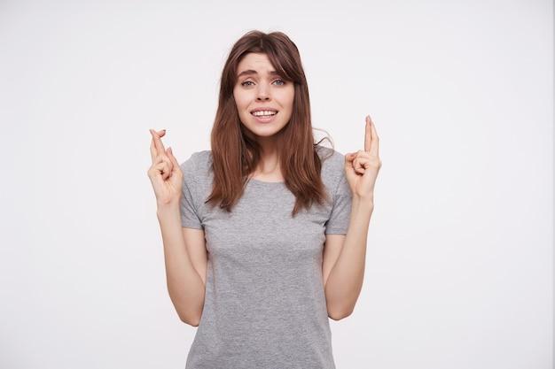 Esperando uma jovem atraente de cabelos escuros com penteado casual, levantando as mãos com os dedos cruzados enquanto olha preocupadamente para a câmera, isolada sobre fundo branco