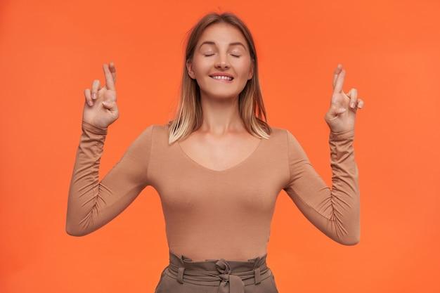 Esperando uma jovem loira de cabelos curtos de aparência agradável com maquiagem natural mordendo preocupantemente o lábio inferior enquanto faz um desejo e cruza os dedos para dar sorte, isolada sobre a parede laranja