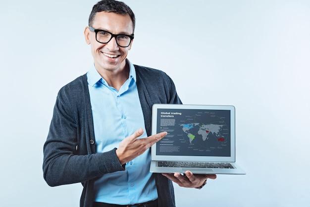 Esperando você se juntar a mim. empresário de aparência amigável em smart casual sorrindo para a câmera enquanto aponta em direção a uma tela de computador com um mapa global de transferências comerciais.