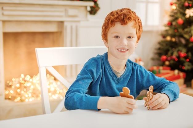 Esperando você se juntar a mim. garoto adorável alegre com os olhos cheios de emoção enquanto se diverte e brinca com biscoitos caseiros.