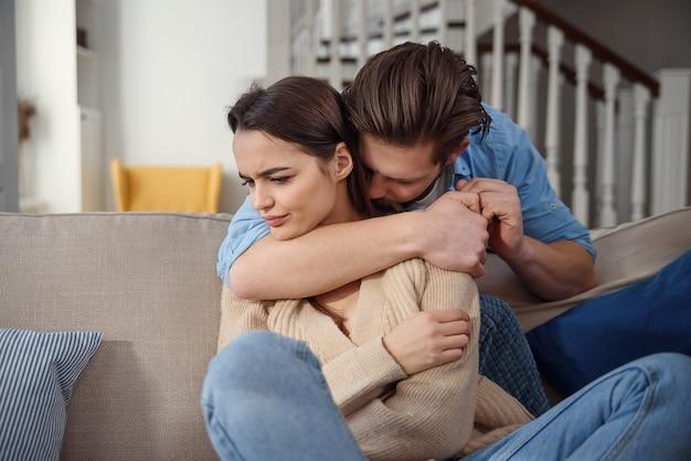 Esperar. jovem preocupado está consolando sua namorada enquanto toca seu braço suavemente. mulher está segurando o telefone móvel e olhando para o namorado com ofensa