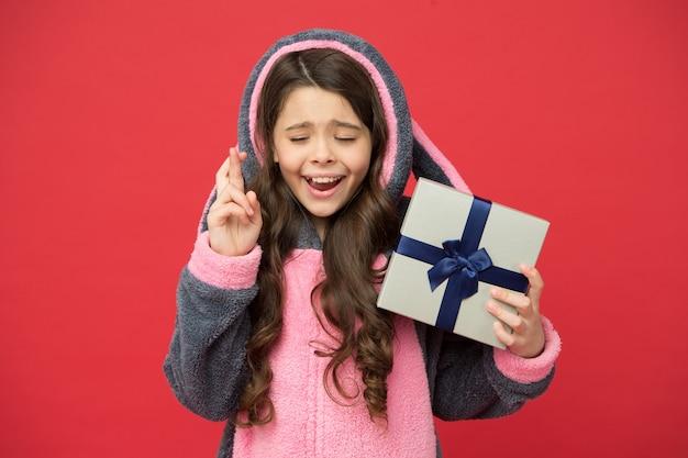 Espere o melhor. menina de pijama de coelhinha. criança em coelho kigurumi. garota feliz em um pijama fofo. conceito de estilo de vida. descanse e relaxe. criança de pijama segura caixa de presente embrulhada. loja e conceito de compras.