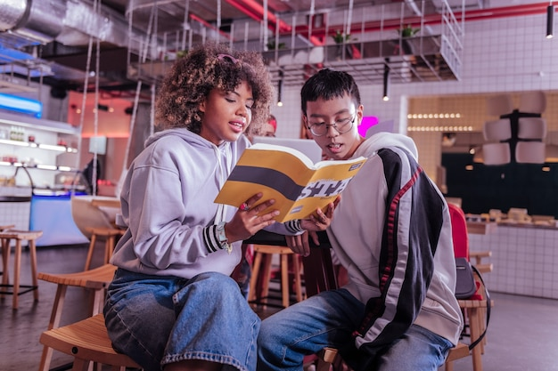 Espere um segundo. homem asiático concentrado usando óculos enquanto olha para o livro