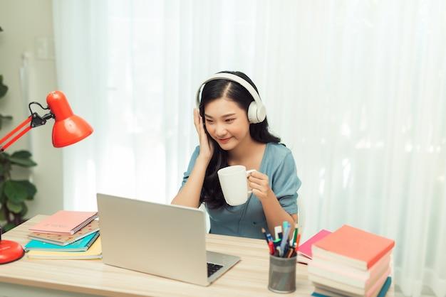 Esperta garota asiática mesa trabalho remoto laptop assistir seminário beber bebida caneca em casa dentro de casa