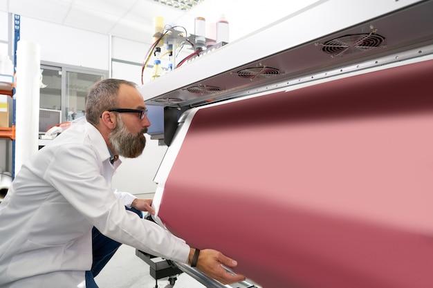 Espertise homem na plotter de indústria de impressão de transferência