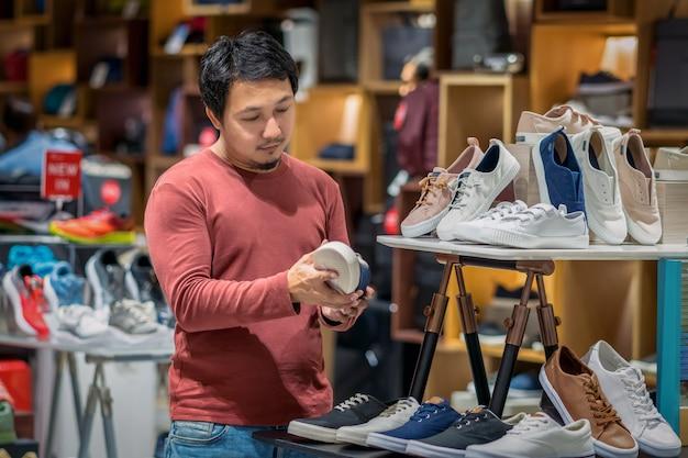 Esperto homem asiático com barba escolhendo sapatos da moda em loja de loja no centro comercial de departamento