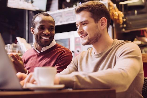 Espertos e alegres dois colegas trabalhando juntos enquanto um homem afro-americano está sorrindo e olhando para seu colega