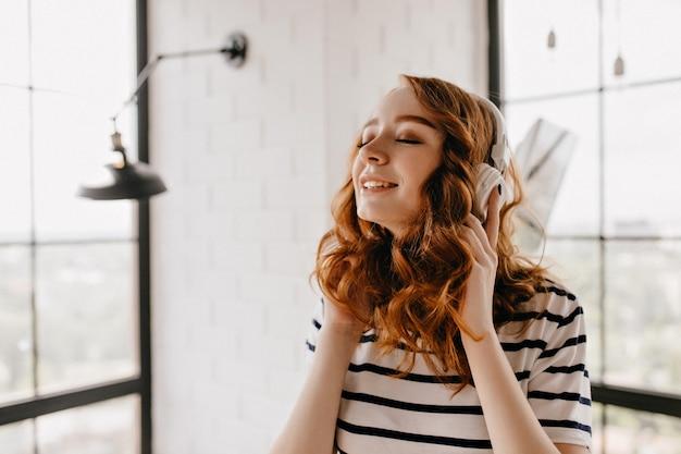 Espetacular garota encaracolada ouvindo música com os olhos fechados. linda senhora ruiva posando em casa em fones de ouvido.